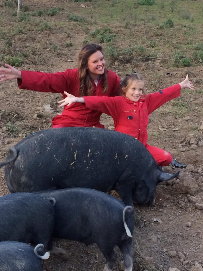 women and a girl wearing red jackets with black pigs