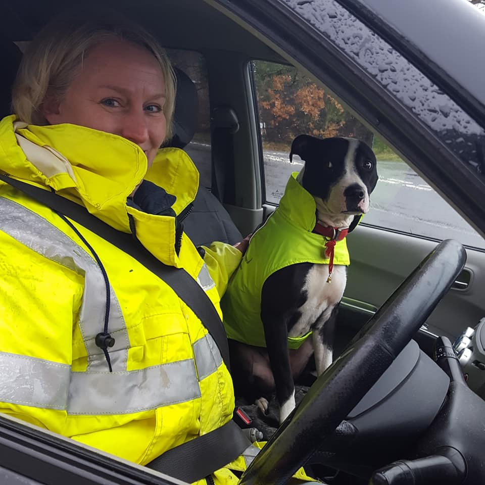 Helen and Murphy sitting in a car wearing high vis jackets